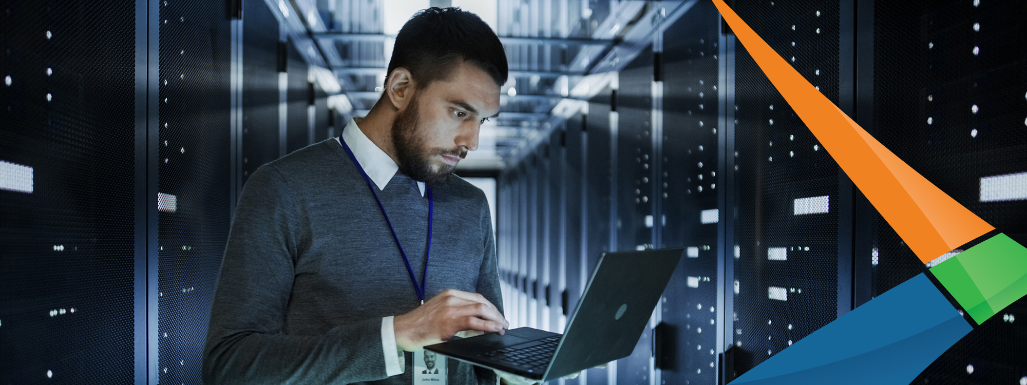 man with beard in server room on laptop